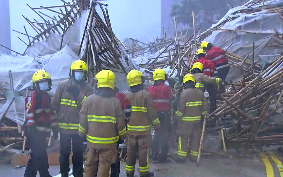 """In this image made from video provided by TVB, firefighters work at the scene of a section of an apartment building scaffolding that collapsed during heavy weather in Hong Kong, Friday, Oct. 8, 2021. The official Hong Kong Observatory issued a Black Rainstorm Signal Friday, which indicates rainfall of more than 70 millimeters (2.76 inches) per hour all over the territory, and instructed people to """"stay indoors or take shelter in a safe place"""". (TVB via AP Video)"""