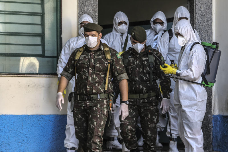 SAO GONÇALO, BRAZIL - MAY 13: Members of the military get out the Health Clinic Nossa Senhora das Vitórias to perform a cleaning work, in Ze Garoto neighborhood during the coronavirus (COVID-19) pandemic on May 13, 2020 in Sao Goncalo, Brazil. According to the Brazilian Health Ministry, Brazil has over 175,000 positive cases of coronavirus (COVID-19) and more than 12.500 deaths. (Photo by Luis Alvarenga/Getty Images)