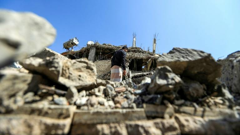 A Yemeni walks past a building destroyed in a Saudi-led coalition airstrike