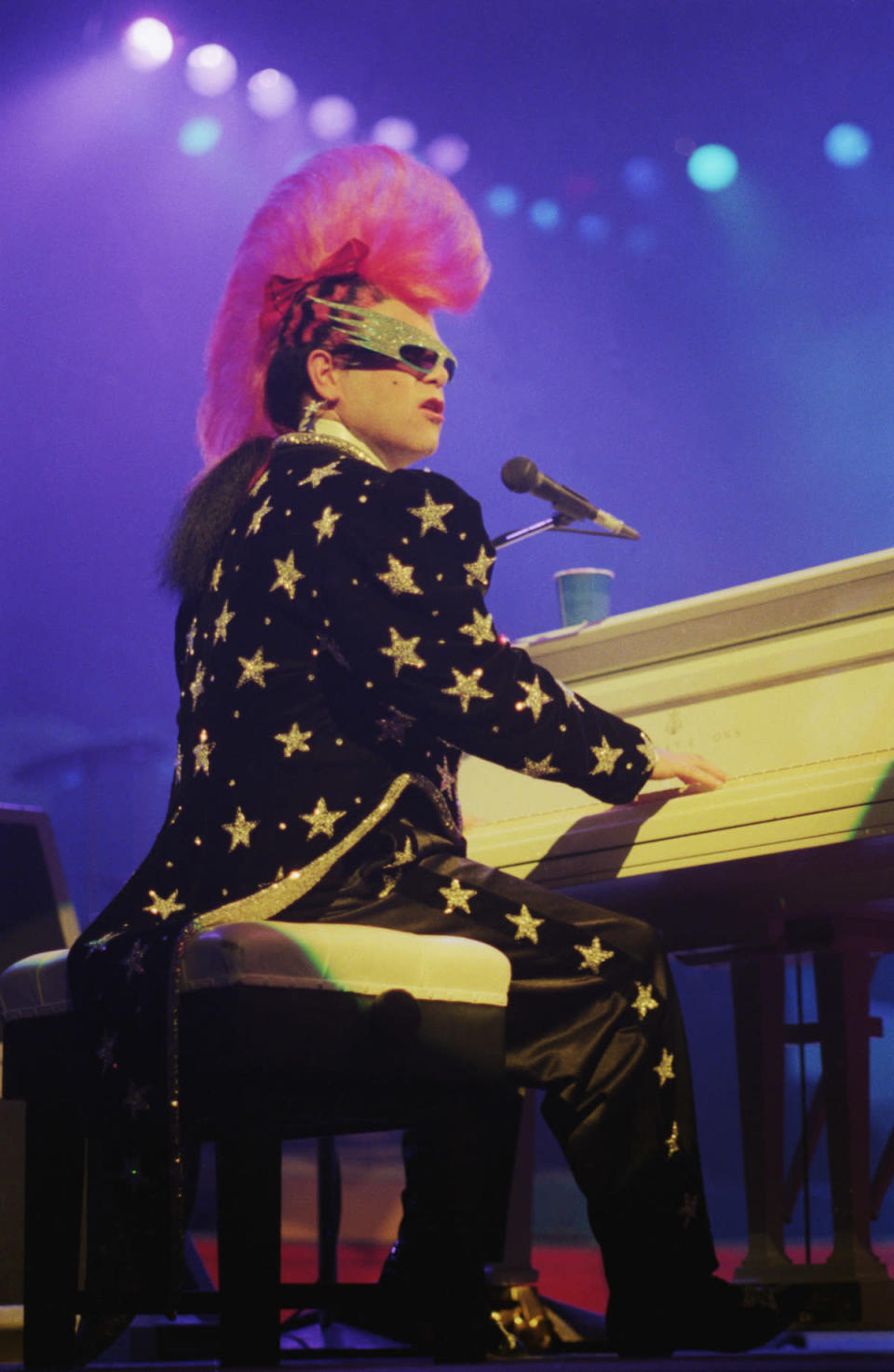 <p>Elton John performs wearing a purple mohawk and velvet star suit in 1986. (Photo: Getty Images) </p>