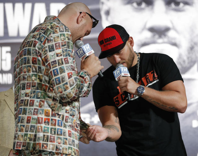 Tom Schwarz, right, of Germany, looks at the suit of Tyson Fury, of England, during a news conference for their upcoming fight Wednesday, June 12, 2019, in Las Vegas. The two are scheduled to fight in a heavyweight bout Saturday in Las Vegas. (AP Photo/John Locher)