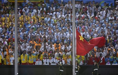 A paramilitary police officer raises the Chinese national flag out in a flag-raising ceremony during the 2014 Nanjing Youth Olympic Games opening ceremony, in Nanjing, Jiangsu province, August 16, 2014. REUTERS/Aly Song
