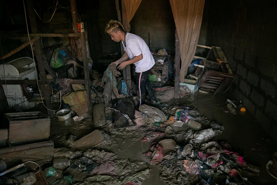 FILE PHOTO: A man goes through his belongings inside a house covered with mud after flooding caused by Typhoon Ulysses (international name Vamco) in Marikina on November 13, 2020. (Source: REUTERS/Eloisa Lopez)