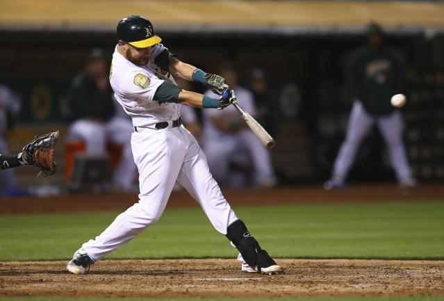 Oakland Athletics' Jonathan Lucroy drives in the winning run against San Francisco Giants in the 11th inning of a baseball game Saturday, July 21, 2018, in Oakland, Calif. The A's won 4-3. (AP Photo/Ben Margot)