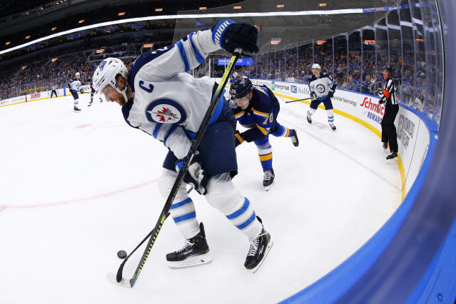Winnipeg Jets winger Blake Wheeler (26) fights St. Louis Blues center Oskar Sundqvist (70), of Sweden, for control of the puck during the third period of an NHL hockey game Sunday, Dec. 29, 2019, in St. Louis. (AP Photo/Dilip Vishwanat)
