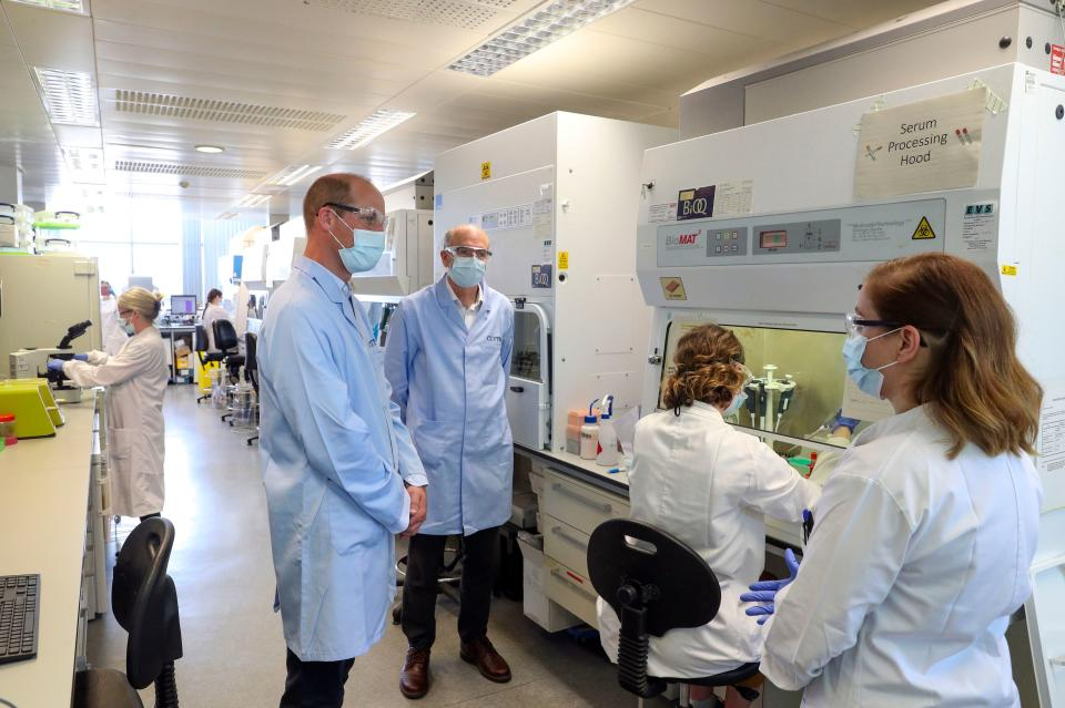 Britain's Prince William, Duke of Cambridge (2L), wearing PPE (personal protective equipment), of a face mask or covering, eye protection and an overall as a precautionary measure against spreading COVID-19, meets scientists including Christina Dold (R) during a visit to the manufacturing laboratory where a vaccine against the novel coronavirus COVID-19 has been produced at the Oxford Vaccine Group's facility at the Churchill Hospital in Oxford, west of London on June 24, 2020, during a visit to learn more about their work to establish a viable vaccine against coronavirus. (Photo by Steve Parsons / POOL / AFP) (Photo by STEVE PARSONS/POOL/AFP via Getty Images)