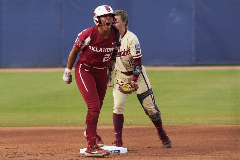 Oklahoma's Tiare Jennings, left, celebrates at second base next to Florida State' Josie Muffley after a double in the first inning of the second game of the NCAA Women's College World Series softball championship series Wednesday, June 9, 2021, in Oklahoma City. (AP Photo/Sue Ogrocki)