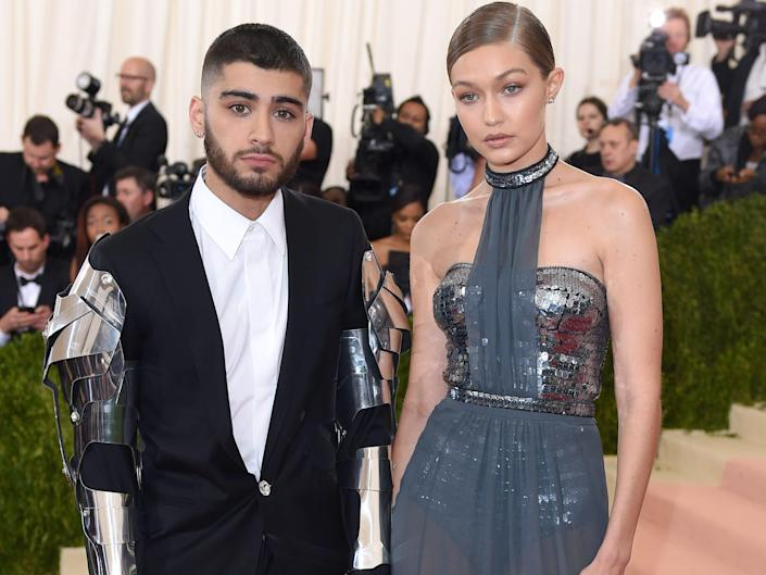 Zayn Malik at the 2016 Met Gala wearing a suit with metal armor on the arms with gigi hadid next to him in a blue gown