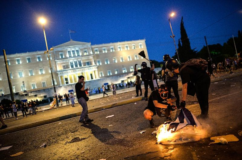 Protesters burn a Greek flag in central Athens, during an anti-austerity protest on July 15, 2015 (AFP Photo/Andreas Solaro)