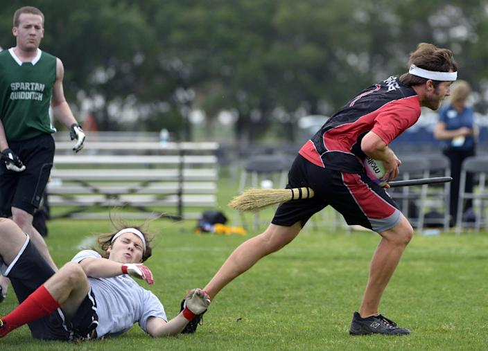 Silicon Valley Skrewts' Greg Weber, right, slips away from Rollins College's Stephen Nettles during a scrimmage at the Quidditch World Cup in Kissimmee, Fla., Friday, April 12, 2013. Quidditch is a game born within the pages of Harry Potter novels, but in recent years it's become a real-life sport. The game is a co-ed, full contact sport that combines elements of rugby, dodgeball and Olympic handball. (AP Photo/Phelan M. Ebenhack)