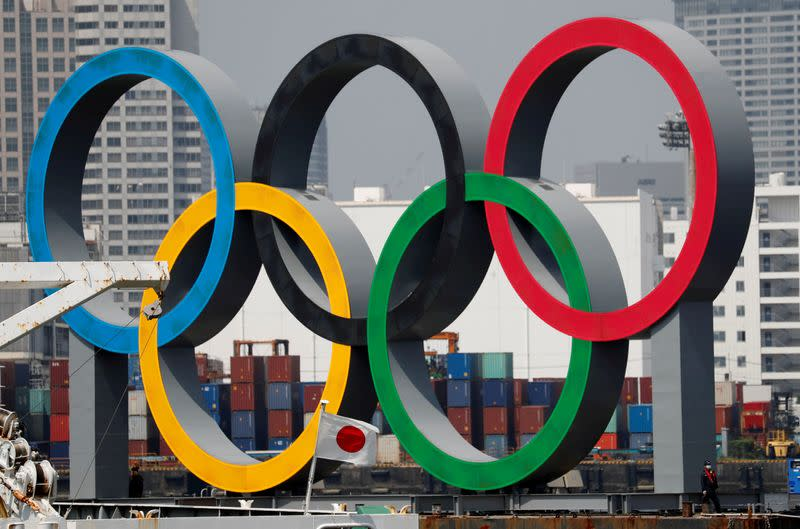 FILE PHOTO: FILE PHOTO: The giant Olympic rings, which are being temporarily removed for maintenance, are seen behind Japan's national flag, at the waterfront area at Odaiba Marine Park in Tokyo