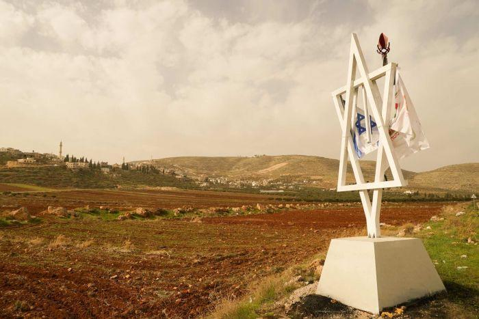 A white star of David statue sits on open land with a city in the background.