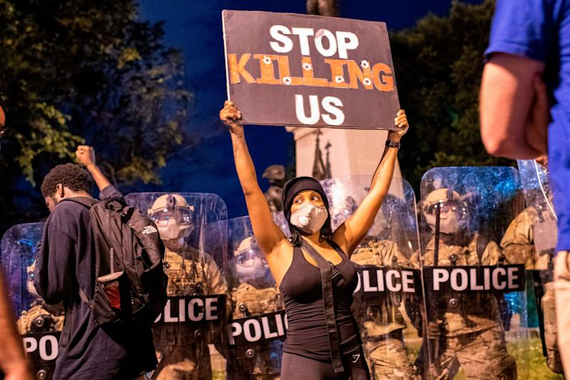 """A demonstrator holds a sign reading """"Stop Killing Us"""" in front of a police line outside of the White House on May 30, 2020."""