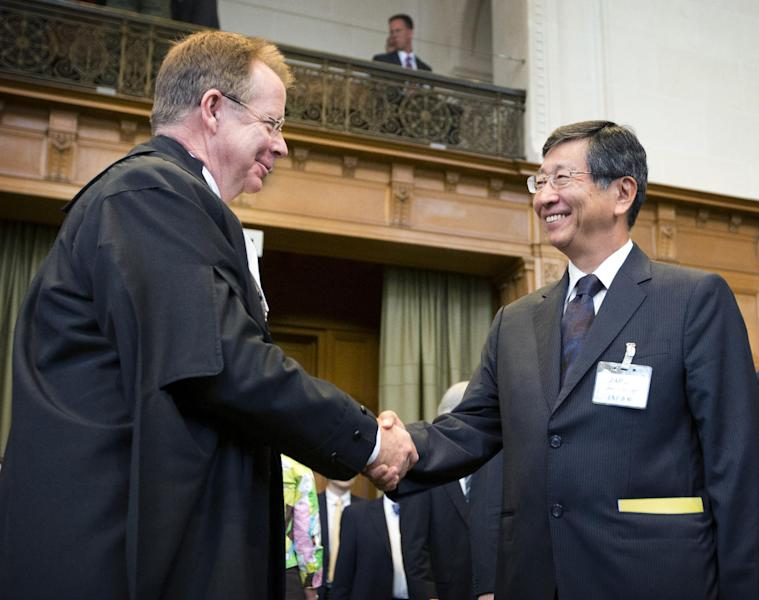 CORRECTS ID OF PERSON AT LEFT General Counsel Bill Campbell, left, shakes hands with Japanese Deputy Minister of Foreign Affairs Koji Tsuruoka at the International Court of Justice (ICJ) in The Hague, Netherlands, Wednesday, June 26, 2013. Australia is urging the United Nations' highest court to ban Japan's annual whale hunt. Lawyers for Australia will argue at the ICJ on Wednesday that Japan harpoons minke whales each year in the icy waters around Antarctica in breach of a 1986 moratorium on commercial whaling. Japan will respond next week by telling judges that the hunt is for scientific research and is allowed under the 1946 International Convention for the Regulation of Whaling. The court will take months to issue a final and binding decision. (AP Photo/Jiri Buller)