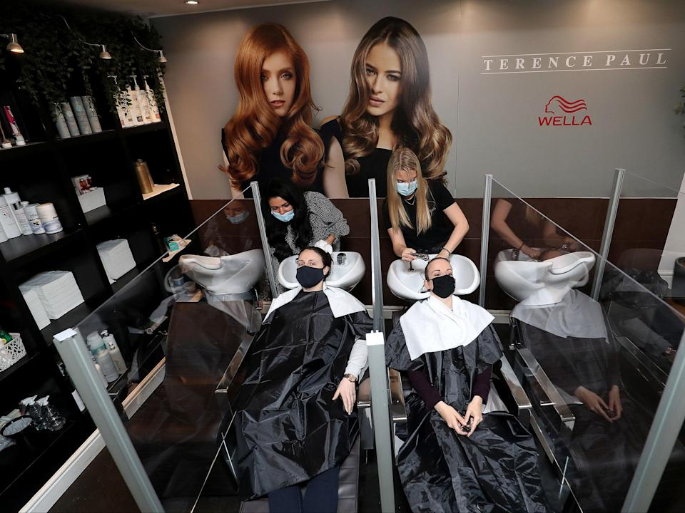 Louise Boothby (left) and Chloe Travis have their hair washed at the reopening of Terence Paul Hair Salon in Knutsford, Cheshire (PA)