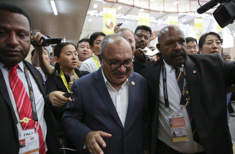 Papua New Guinea Prime Minister Peter O'Neill is escorted by security as he is chased by reporters after reading his statement at the end of the APEC 2018 summit at Port Moresby, Papua New Guinea on Sunday, Nov. 18, 2018. (AP Photo/Aaron Favila)