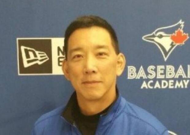 John Hashimoto, 56, of Hamilton faces a child luring charge and another offence. He formerly worked for the Toronto Blue Jays' youth academy. (johnhashimoto.ca - image credit)
