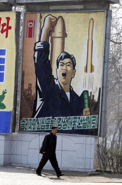"A North Korean man walks past a propaganda billboard in Pyongyang, North Korea, Friday, April 13, 2012. North Korea's much-anticipated rocket launch ended quickly in failure early Friday, splintering into pieces over the Yellow Sea soon after takeoff, according to South Korean and U.S. officials. The slogan reads ""Let's raise the spirits of winners and build a strong and prosperous nation!"" (AP Photo/Ng Han Guan)"