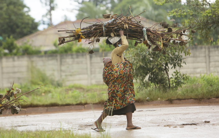 A woman with a baby strapped on her back carries firewood for cooking on the streets of Harare, in this Tuesday, March 2, 2021 photo. From driving trucks and fixing cars to encouraging girls living with disability to find their places in society, women in Zimbabwe are refusing to be defined by their gender or circumstances, even as the pandemic hits them hardest and imposes extra burdens.(AP Photo/Tsvangirayi Mukwazhi)