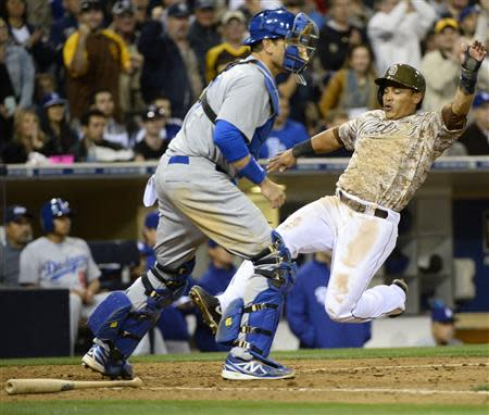 Mar 30, 2014; San Diego, CA, USA; San Diego Padres shortstop Everth Cabrera (2) scores ahead of a play by Los Angeles Dodgers catcher A.J. Ellis (17) in the eighth inning on the opening day baseball game at Petco Park. Christopher Hanewinckel-USA TODAY Sports