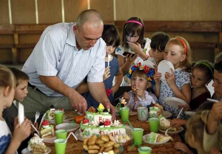 Children wait before taking a piece of a cake during a birthday party in Ukraine, July 30, 2015. (Reuters)