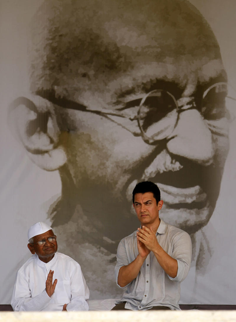 """FILE-In this Aug. 27, 2011 file photo, Bollywood actor Aamir Khan, right, sits with India's anti-corruption activist Anna Hazare during the 12th day of Hazare's hunger strike against corruption in New Delhi, India. Bollywood megastar Khan is making India confront its dark side. Shining light on inequities like the rampant abortion of female fetuses, caste discrimination and the slaying of brides in dowry disputes, actor Khan has reached an estimated one-third of the country with a new TV talk show """"Satyamev Jayate"""", or """"Truth Alone Prevails,"""" that tackles persistent flaws of modern India that most of its citizens would prefer to ignore.(AP Photo/Rajesh Kumar Singh, File)"""