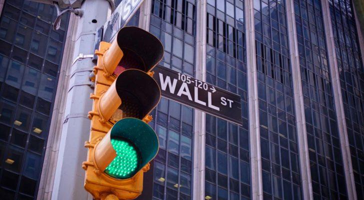 A traffic light flashes green in front of Wall Street.