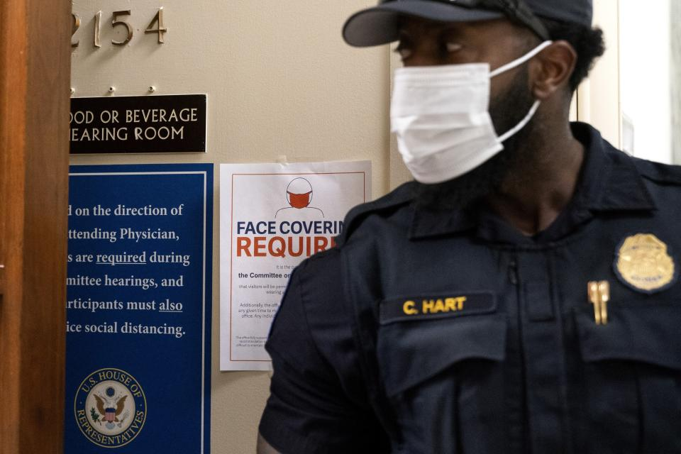 A member of the Capitol Police wears a face mask by a sign stating that face coverings are required, outside a House Committee on Oversight and Reform hearing, Thursday, July 29, 2021, on Capitol Hill in Washington. (AP Photo/Jacquelyn Martin)