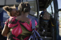 FILE - In this Sept. 22, 2021, file photo a child sleeps on the shoulder of a woman as they prepare to board a bus to San Antonio moments after a group of migrants, many from Haiti, were released from custody upon crossing the Texas-Mexico border in search of asylum in Del Rio, Texas. In the past week, the push to change the nation's immigration laws and create a path to citizenship for young immigrants brought illegally to the country as children faced a serious setback on Capitol Hill. Bipartisan negotiations to overhaul policing collapsed and searing images of Haitian refugees being mistreated at the U.S.-Mexico border undermined President Joe Biden's pledge of humane treatment for those seeking to enter the United States. (AP Photo/Julio Cortez, File)