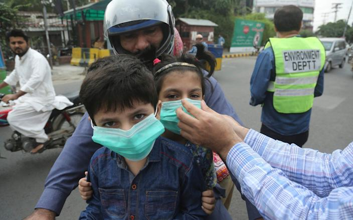 An official hands masks to children in Lahore - AP