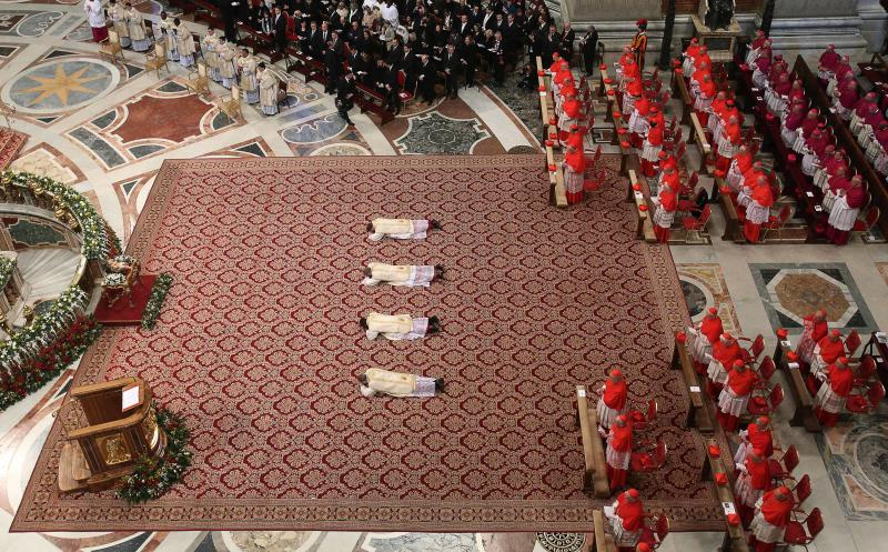 From left to right, Angelo Vincenzo Tani, of Italy, Fortunatus Nwachukwu, of Nigeria, Georg Ganswein, of Germany, and Nicolas Marie Denis Thevenin lie on the ground as they are named bishops during an Epiphany mass celebrated by Pope Benedict XVI in St.Peter's Basilica at the Vatican, Sunday, Jan. 6, 2013. The Epiphany day, is a joyous day for Catholics in which they recall the journey of the Three Kings or Magi to pay homage to Baby Jesus. (AP Photo/Alessandro Di Meo, Pool)