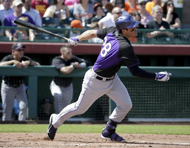 Colorado Rockies' Nolan Arenado watches his RBI single after the game during the third inning of a spring exhibition baseball game in Scottsdale, Wednesday, March 26, 2014. (AP Photo/Chris Carlson)