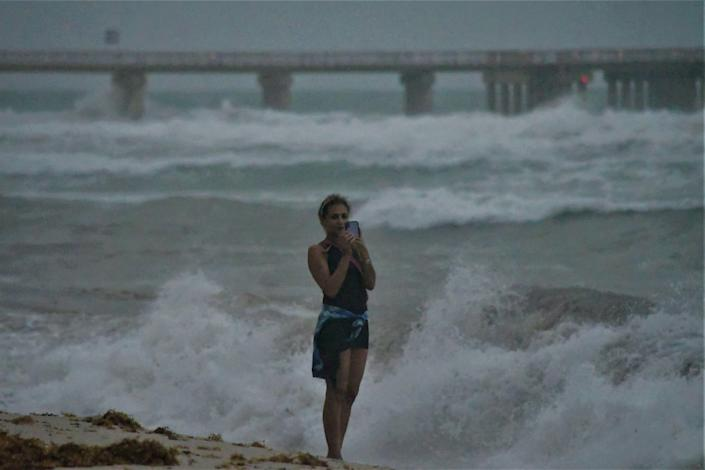 A woman grabs a selfie to remember then Hurricane Isaias near Miami. Photo by Paul Scicchitano.