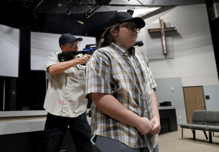 In this July 21, 2019 photo, Brett Faulkner, left, fires blanks out of an assault rifle as he and Julia Gant, right, participate in a hostage-taking scenario during a security training session at Fellowship of the Parks campus in Haslet, Texas. An industry has sprung up following mass shootings at houses of worship around the country to train civilians to protect their churches with the techniques and equipment of law enforcement. (AP Photo/Tony Gutierrez)