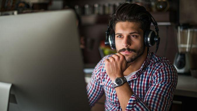man listening to the music while working on a computer.