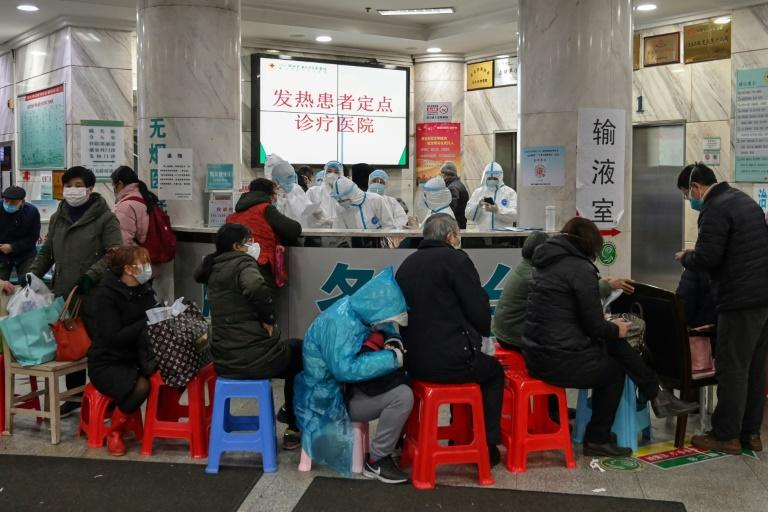People wait to see medical staff (back) in protective clothing at Wuhan Red Cross Hospital, in the Chinese city at the epicentre of the coronavirus epidemic