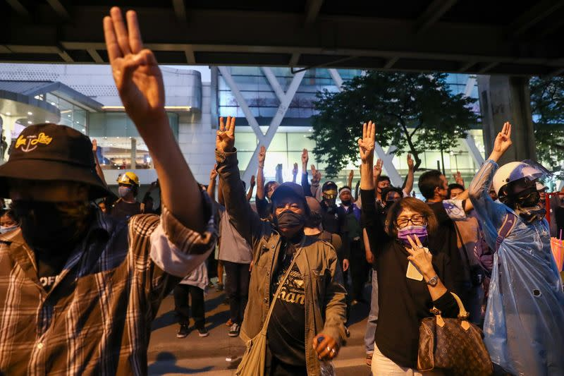 Demonstrators show the three-fingered salute during a rally in Bangkok