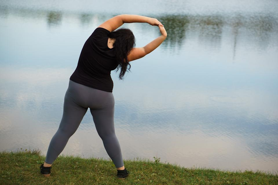 Young woman in sportswear doing yoga exercises near the lake. Healthy lifestyle, sport, weight losing, activity concept