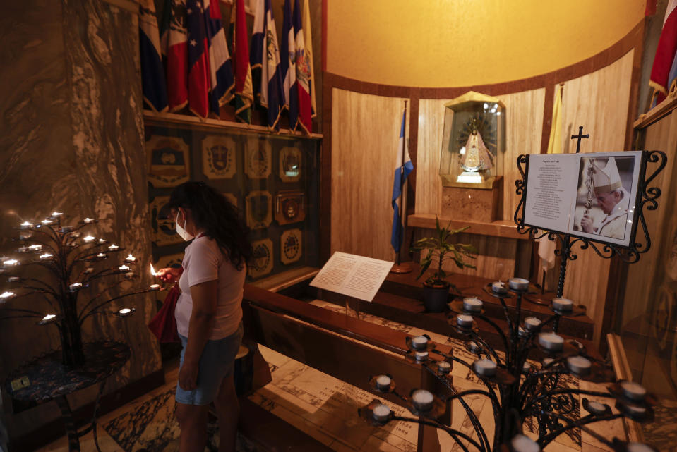A woman lights a candle past a portrait of Pope Francis in the Argentine church of Santa Maria Addolorata (Our Lady of Sorrows) in Rome, Sunday, July 4, 2021. Pope Francis has been hospitalized for a scheduled surgery for a stenosis, or restriction, of the large intestine, the Vatican said. The news came just three hours after Francis had cheerfully greeted the public in St. Peter's Square and told them he will go to Hungary and Slovakia in September. (AP Photo/Riccardo De Luca)