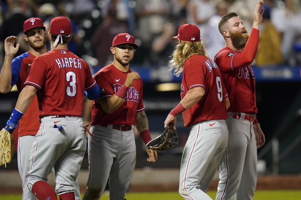 Philadelphia Phillies' Bryce Harper (3) and Travis Jankowski (9) celebrate with teammates after the second baseball game of a doubleheader against the New York Mets Friday, June 25, 2021, in New York. (AP Photo/Frank Franklin II)