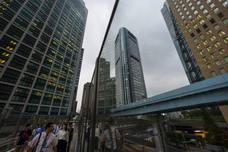 People walk in shadows of office skyscrapers in business district in Tokyo