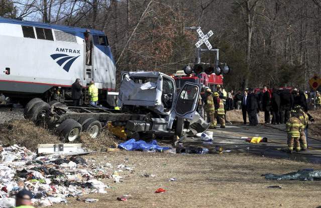 <p>Emergency personnel work at the scene of a train crash involving a garbage truck in Crozet, Va., on Jan. 31, 2018. (Photo: Zack Wajsgrasu/The Daily Progress via AP) </p>