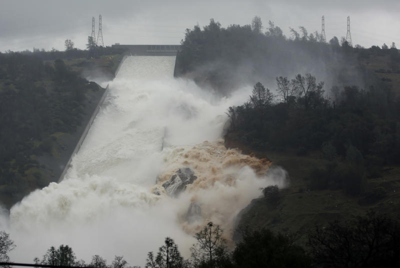 FILE - In this Feb. 9, 2017 file photo, water flows through a break in the wall of the Oroville Dam spillway in Oroville, Calif. One year after the closest thing to disaster at a major U.S. dam in a generation, federal dam regulators say they are looking hard at how they overlooked the built-in weaknesses of old dams like California's Oroville Dam for decades, and expect dam managers around the country to study their old dams and organizations equally hard. (AP Photo/Rich Pedroncelli, file)