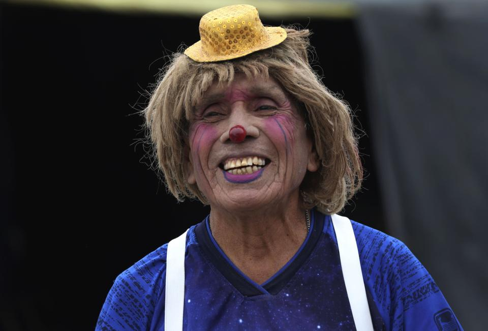 """Circus clown Santos Chiroque, whose performance name is """"Piojito,"""" or Little Tick, laughs at his grandchild's comment that he looks like a woman, as he shows off his clown costume outside his home on the outskirts of Lima, Peru, Monday, Aug. 10, 2020. Chiroque's family used to run their own small circus, but since March when the lockdown to curb COVID-19 closed their business, and the requirement for people over 60 to self-quarantine kept the 74-year-old at home, they started selling circus food like caramelized apples to survive. (AP Photo/Martin Mejia)"""