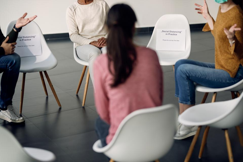 Unrecognizable attenders of group therapy talking while sitting on safe distance due to COVID-19 pandemic.
