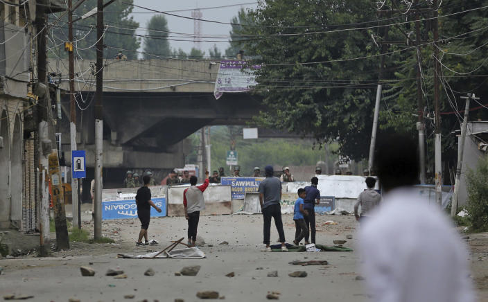 Kashmiri protesters challenge paramilitary soldiers during a protest against the Indian government in Srinagar, India, Friday, Aug. 9, 2019. The predominantly Muslim area has been under an unprecedented security lockdown and near-total communications blackout to prevent unrest and protests after India's Hindu nationalist-led government said Monday it was revoking Kashmir's special constitutional status and downgrading its statehood. (AP Photo/Altaf Qadri)