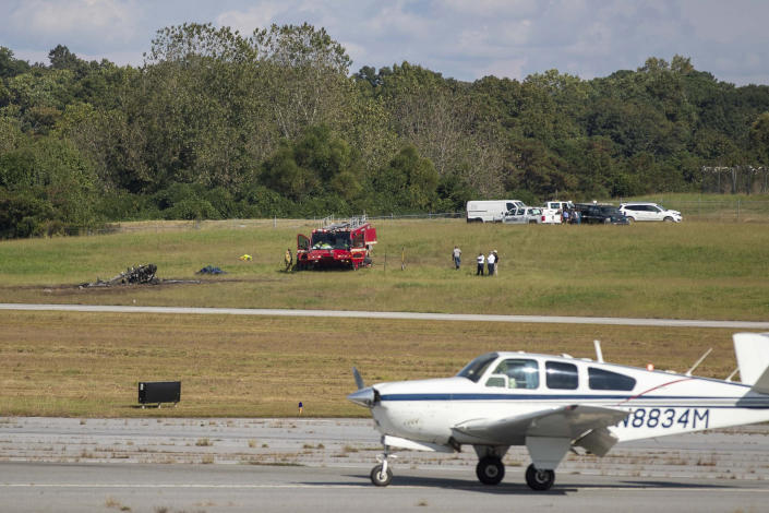 Emergency Response teams work the scene of a fatal small plane crash at DeKalb-Peachtree Airport, Friday, Oct. 8, 2021, in DeKalb County, Ga., as another small aircraft is seen in the foreground. (Alyssa Pointer/Atlanta Journal-Constitution via AP)