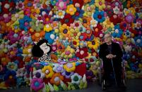 """FILE - In this Sept. 15, 2014 file photo, Argentine cartoonist Joaquin Salvador Lavado, better known as """"Quino,"""" poses next to his character Mafalda at the exhibition, The World According to Mafalda, in Buenos Aires, Argentina. Lavado passed away on Wednesday, Sept. 30, 2020, according to his editor Daniel Divinsky who announced it on social media. (AP Photo/Natacha Pisarenko, File)"""