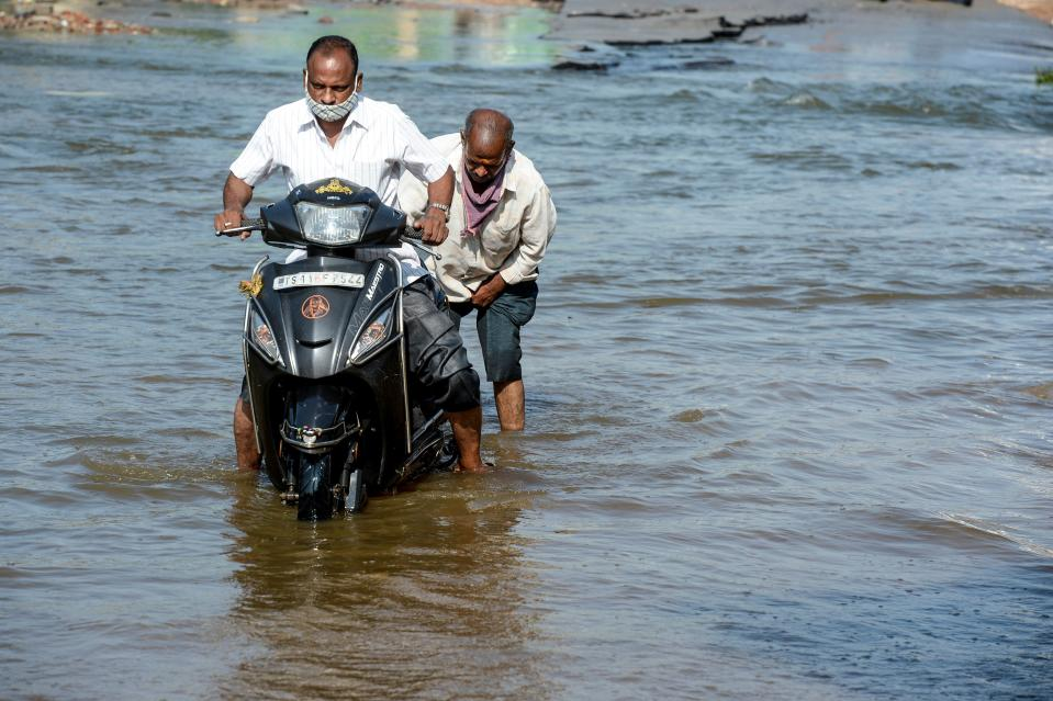 Motorists make their way on a flooded street following heavy rains in Hyderabad on October 16, 2020. (Photo by NOAH SEELAM / AFP) (Photo by NOAH SEELAM/AFP via Getty Images)