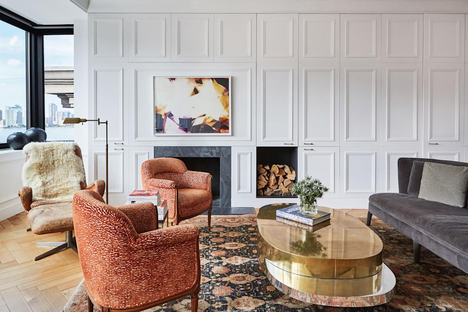Blinken found her favorite piece in the apartment, a 1970s Gabriella Crespi coffee table with expandable sides, in London. The contemporary sofa contrasts with the vintage orange chairs. The rug is from a Bonhams auction in Los Angeles. On the living room walls, a repetition of the Parisian-style cabinetry can be seen.